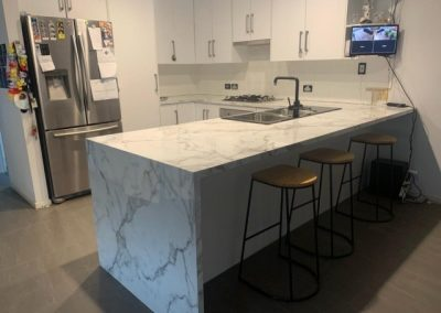 A marble look laminate benchtop installed with a bar featuring a laminate side